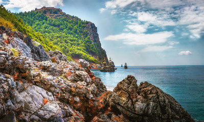 Landscape of rocky mountains and sea on coastline. Bay with ships in tropical Mediterranean Sea. Turkish nature