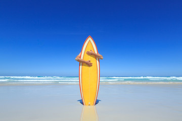 Hugging a surfboard.