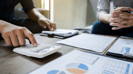 Business executives analyzing on valuation data paper with calculator