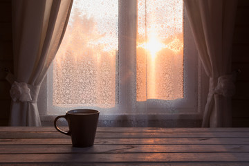 Cup of black coffee or tea in front of the window on the wooden table. Copy space. Romance sunset.