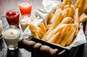 french fries in basket with sauce dipping