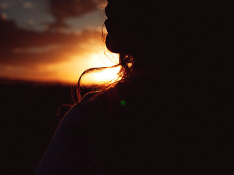 Closeup profile of a woman against the sunset
