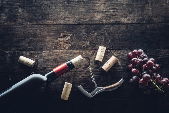 Bottle of wine, corks and grapes on wooden background