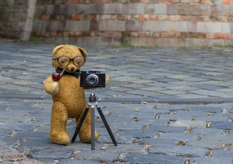 Old teddy bear teking pictures with an old machine on the street