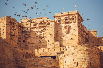 Poster de jardin Fortification Birds flying over the towers of historical Jaisalmer fort with monumental stone walls in old city of Rajasthan, India