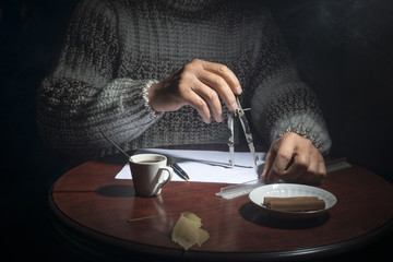 Male hands, at the table and write a pen on a piece of paper on a dark background
