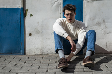 Young man sitting on a wall