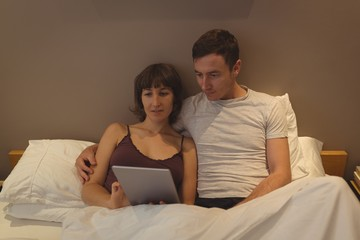 Couple using digital tablet in bedroom