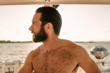 A shirtless man on a sailboat