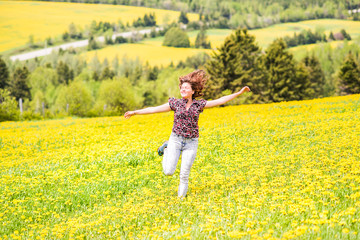 Young woman running, jumping in air and smiling on countryside yellow dandelion flower fields in summer grass in Ile D'Orleans, Quebec, Canada smiling