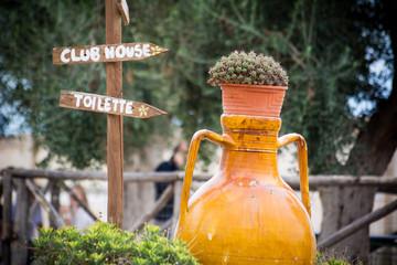 a public toilet signboard near a big terracotta pot