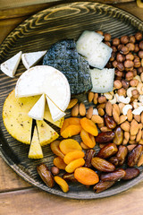 country food, health, lifestyle concept. on nice wooden tray there is wide variety of snakes presented in different cheeses, three types of nuts and such dried fruits as apricots and dates