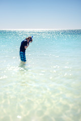 Boy standing in clear water with snorkel set and board shorts on a clear summer day