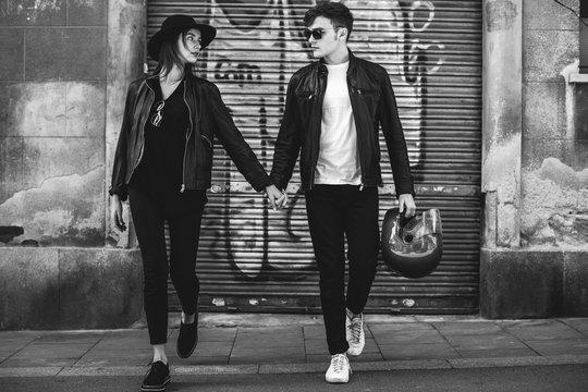 Biker couple holding hands walking on the street.