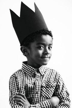 Portrait of a boy wearing a black crown.