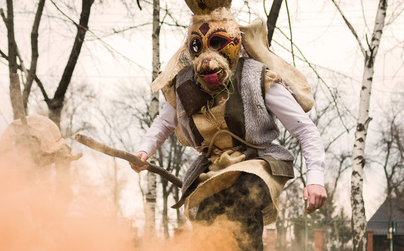 Male dressed in old pagan slavic dress jumping out form smoke and fire casting out evil  powers