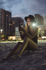 Rio de Janeiro. Brazil. Woman using mobile phone while sitting on the beach at sunset