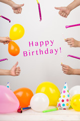birthday, occasion, anniversary concept. arms with thumbs up, symbol of like, with balloons and candles are atretching in the center where text of congratulation is