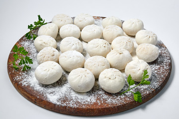 Khinkali on wooden plate with flour. Pelmeni