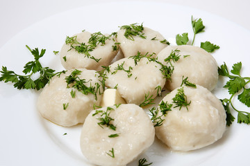 Khinkali on white plate with parsley and  dill