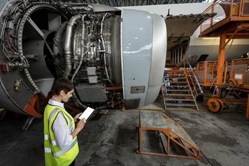 Female aircraft maintenance engineer examining turbine engine of