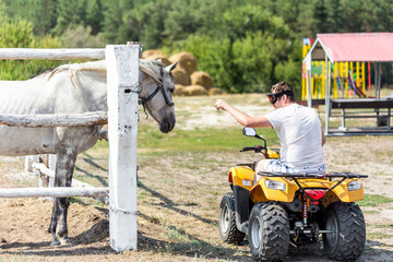 Caucasian man on ATV quad bike meet beautiful white horse on a farm or ranch. Evolution of vehicles for centuries concept. Past and present progress