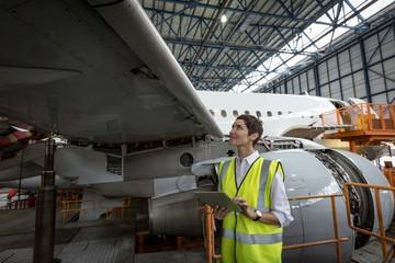 Female aircraft maintenance engineer examining engine of