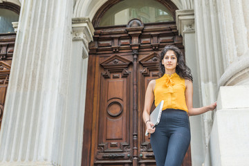 Modern East Indian American Lawyer. Wearing sleeveless orange shirt, arm carrying laptop computer, a young business lady standing by vintage style office building, greeting you, beginning of work day.