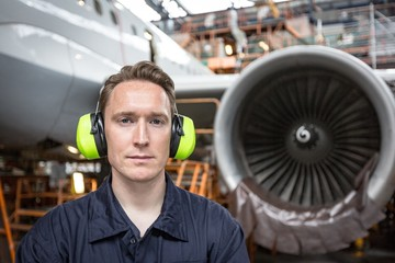 Male aircraft maintenance engineer standing at airlines