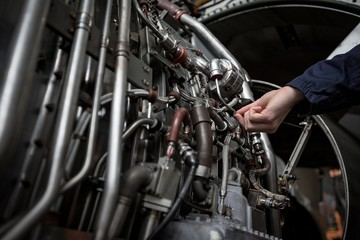 Male aircraft maintenance engineer examining turbine engine of