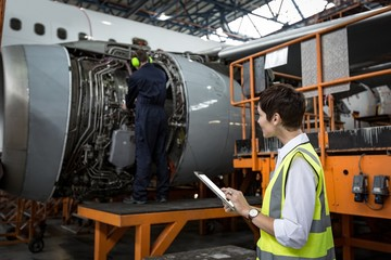 Male aircraft maintenance engineers examining turbine engine of