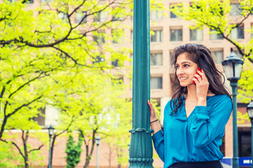 East Indian American Business Woman Calling Outside in spring day. Wearing long sleeve, V neck shirt, a beautiful college student standing by light pole, smiling, listening, talking on mobile phone..