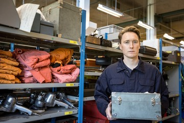Male aircraft maintenance engineer holding tool kit at airlines