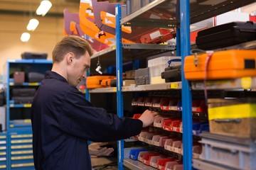 Male aircraft maintenance engineer examining various work tool