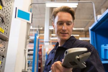 Male aircraft maintenance engineer examining work tool