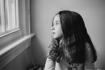 Cute young girl looking bored while peeking out a window