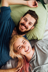 Happy Couple In Smling While Lying in Bed