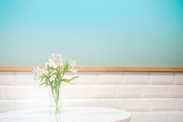 Beautiful white flower in glass vase on turquoise background and white crick tiles wall. Festive greeting card