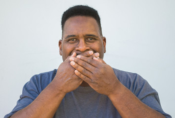 close up of black man with hands covering mouth-speak no evil