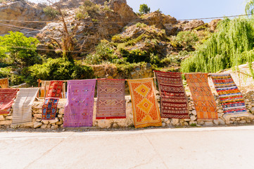 Hand woven rugs hang from a wall in Asgaour, Morocco