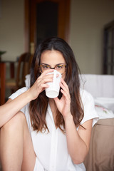 Woman drinking coffee while looking at camera