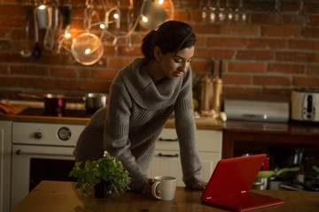 Young woman using laptop in kitchen