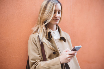 Blond woman in the city with a cell phone