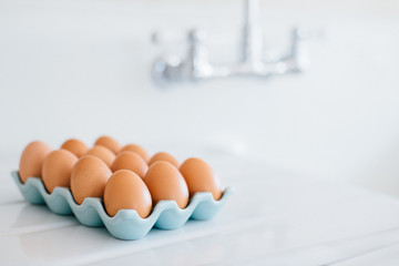 Brown chicken eggs displayed on an enamel countertop