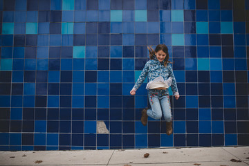 Jumping girl in front of blue wall