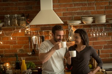 Couple having coffee in kitchen