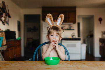 Toddler child eating baby carrots while wearing bunny ears.