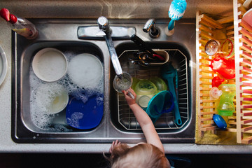 Young toddler child washing dishes in the kitchen.
