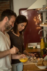 Young couple preparing food in kitchen