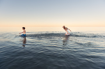 Girl chasing and splashing her brother in calm water at dusk